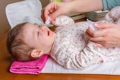 Enfantez les mains nettoyant des yeux de bébé avec du coton images libres de droits