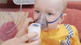 Enfantez les prises le masque sur l'inhalateur de bébé et respirez la médecine à la maison Traite l'inflammation des voies aérien banque de vidéos