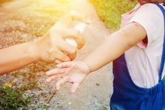 Enfantez les produits répulsifs de pulvérisation d'insecte ou de moustique sur la fille de peau, produit répulsif de moustique po Image libre de droits