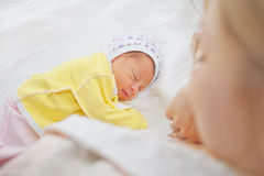 Enfantez les regards et admirez son bébé nouveau-né photo stock