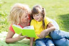 Enfantez lire un livre pour badiner dehors dans l'été Photographie stock