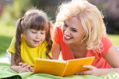 Enfantez lire un livre pour badiner dehors dans l'été Photographie stock libre de droits