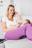 Enfantez parler au téléphone portable tout en alimentant son bébé avec la bouteille à lait Images libres de droits