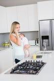 Enfantez parler au téléphone portable tout en portant son bébé dans la cuisine Photos libres de droits