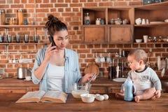 Enfantez parler sur le smartphone et regarder son fils pendant la cuisson du dîner Images libres de droits