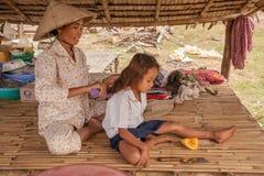 Enfantez peigner la fille sur un canapé sous un auvent Images libres de droits