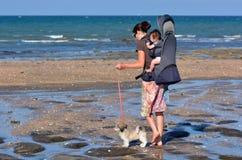 Enfantez portent son bébé et marchent son chien de pavot Photos stock