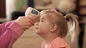 Enfantez prendre la température du ` s de fille utilisant un thermomètre numérique à l'intérieur dans 4k banque de vidéos