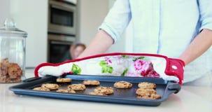 Enfantez prendre les biscuits chauds du four avec la petite fille les sentant banque de vidéos
