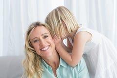 Enfantez se reposer avec sa fille chuchotant un secret Photos stock