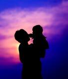 Enfantez tenir le fils sur le fond de ciel de coucher du soleil Image libre de droits