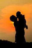 Enfantez tenir le fils sur le fond de ciel de coucher du soleil Image stock