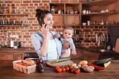 Enfantez tenir son fils sur des bras et parler sur le smartphone pendant la préparation de dîner dans la cuisine Images stock