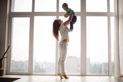 Enfantez tenir son petit garçon dans le ciel Photographie stock