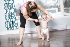 Enfantez tenir un bébé sous ses bras dans le salon image libre de droits