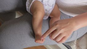 Enfantez toucher de petits orteils de chère fille de bébé banque de vidéos