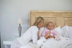 Enfantez vérifier la température en difficulté de fille avec le thermomètre numérique dans la chambre à coucher images stock