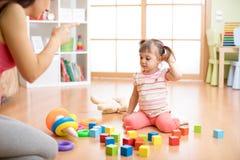 Enfantez voient sa fille jouer haut malpropre de jouets la sensation de salon fâchée et critiquer la fille d'enfant de tristesse  photo stock