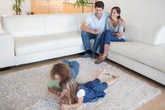 Enfants à l'aide d'un ordinateur de comprimé tandis que leurs parents heureux sont W Image stock