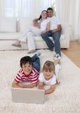 Enfants à l'aide d'un ordinateur portatif sur l'étage dans la salle de séjour Images libres de droits