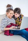 Enfants à l'aide de l'ordinateur portable et se reposant sur le sofa Image stock