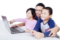 Enfants à l'aide de l'ordinateur portable sur la table avec leur père Photographie stock libre de droits