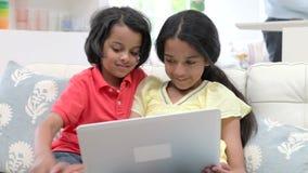 Enfants à l'aide de l'ordinateur portable tout en se reposant sur Sofa At Home banque de vidéos