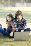 Enfants à l'aide de l'ordinateur portatif dans le stationnement Image stock