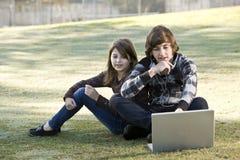 Enfants à l'aide de l'ordinateur portatif dans le stationnement Photos stock