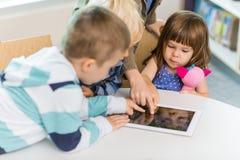Enfants à l'aide de la Tablette de Digital dans la bibliothèque d'école Photos libres de droits