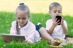Enfants à l'aide de la tablette et du smartphone Photo stock