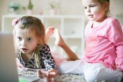 Enfants à l'aide de l'ordinateur portable ensemble à la maison images libres de droits