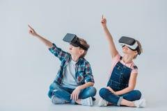 Enfants à l'aide des casques de réalité virtuelle et se dirigeant avec le doigt tout en se reposant Images stock