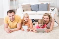Enfants à l'aide des comprimés se trouvant sur le tapis Photos stock