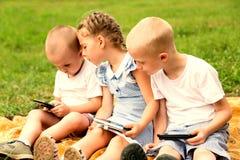 Enfants à l'aide des smartphones Photographie stock
