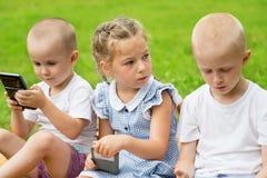 Enfants à l'aide des smartphones se reposant sur l'herbe Photos stock