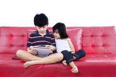 Enfants à l'aide du comprimé électronique ensemble Photographie stock libre de droits