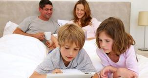 Enfants à l'aide du comprimé dans le lit avec des parents causant derrière clips vidéos