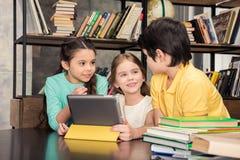 Enfants à l'aide du comprimé numérique et regardant l'un l'autre Images libres de droits