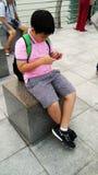 Enfants à l'aide du téléphone portable devant Marina Bay Sands et le paysage urbain Image stock