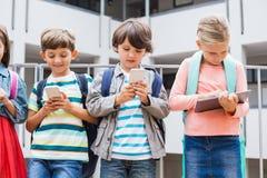 Enfants à l'aide du téléphone portable et du comprimé numérique sur la terrasse d'école Photo stock