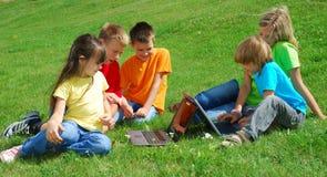 Enfants à l'extérieur avec des ordinateurs portatifs Photographie stock libre de droits