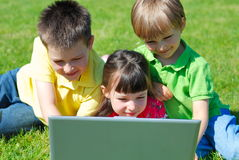 Enfants à l'extérieur avec l'ordinateur portatif Photo libre de droits