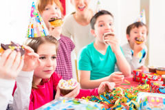 Enfants à la fête d'anniversaire avec les petits pains et le gâteau Photo libre de droits
