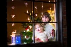 Enfants à la fenêtre le réveillon de Noël Images libres de droits