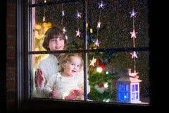 Enfants à la fenêtre le réveillon de Noël Photographie stock libre de droits