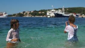 Enfants éclaboussant l'eau, la vie dans une petite station touristique croate Enfants et la mer, concept de voyage clips vidéos