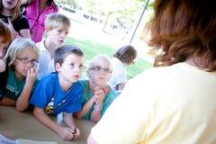 Enfants écoutant une présentation dehors Image libre de droits