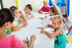 Enfants écrivant ainsi que le tuteur à la classe d'école Photographie stock libre de droits