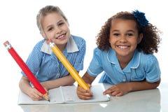 Enfants écrivant leur tâche Photos stock